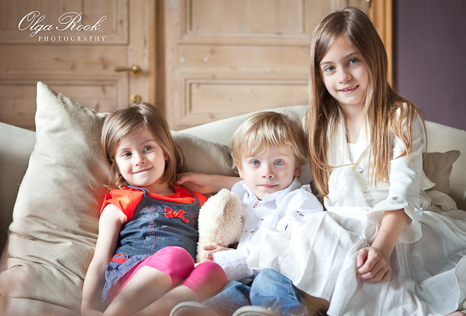 Photo with a group portrait of three children: two girls and a boy sitting next to each other on a sofa in their living room.