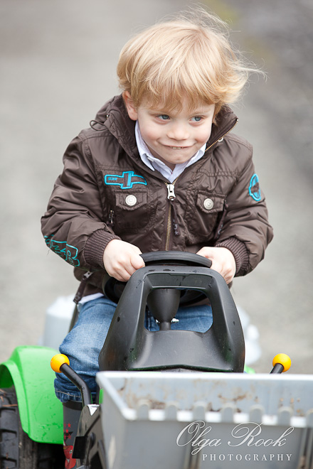 An outdoor portrait of a small boy driving a toy tractor.