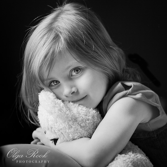 Classic black and white portrait of a small girl embracing her teddybear.