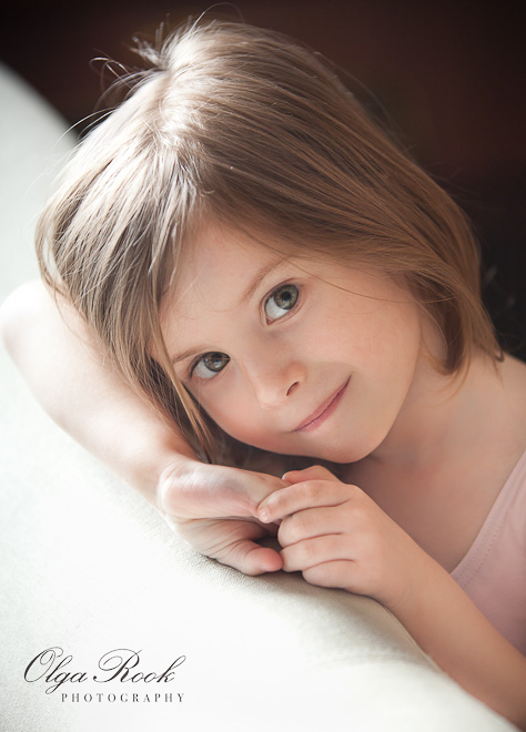 Photo portrait of a little girl in a beautiful gentle light. She looks serene and smart at the same time.