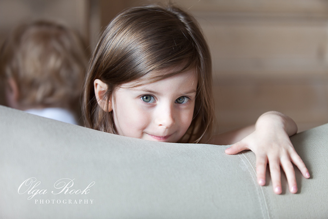 Portrait of a little girl, peeking from behind a sofa.