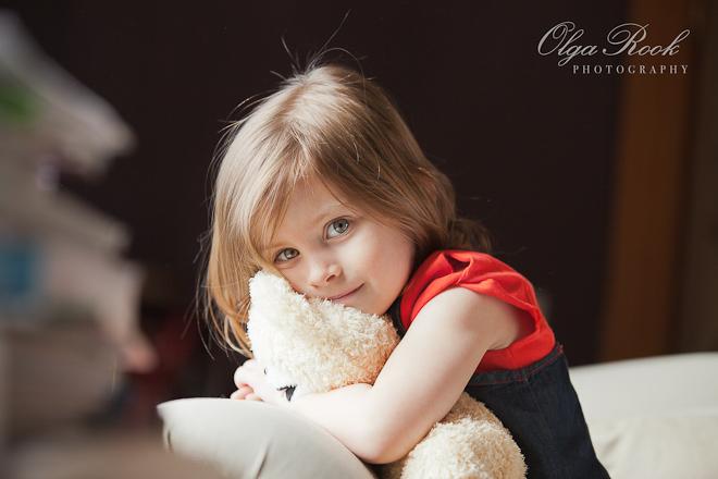 Kleurenfoto van een klein meisje met een knuffelbeest.