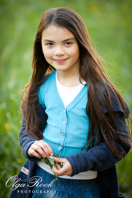 Portrait of a little girl with long dark hair. She charming and confident and is standing in a field, smiling.