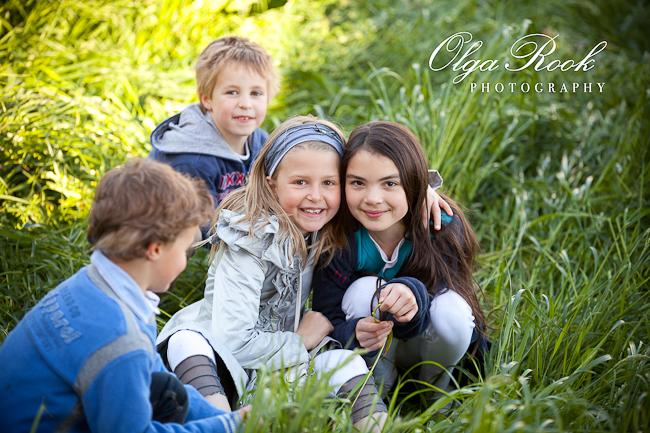 Foto van een groep feestelijk gekleden kinderen zittend in een de hoge gras.