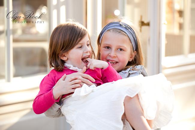 Foto van twee kleine feestelijk geklede meisjes: het oudere mesije draagt de kleinere in haar handen.