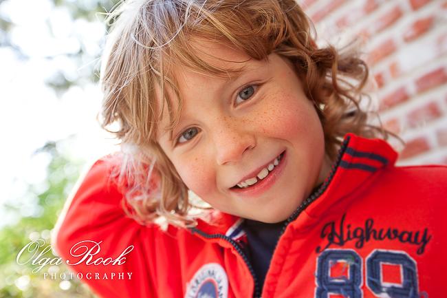 Portret van een lieve en vrolijke jongentje: velle kleuren en lens flair van het tegenlicht.