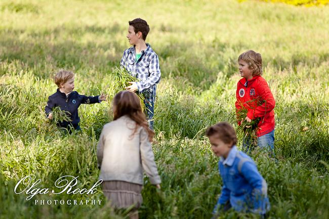 Foto van een groep kinderen die lopen en spelen op een groene grasveld.