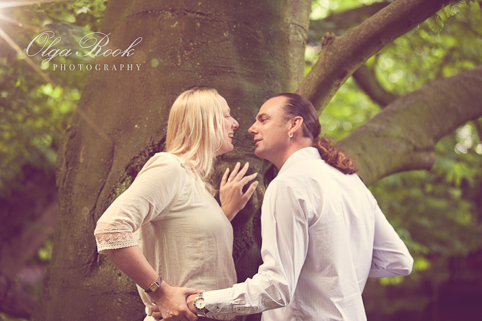A romantic portrait of a beautiful couple in a forest. Their faces come close to each other: a kiss is about to follow.