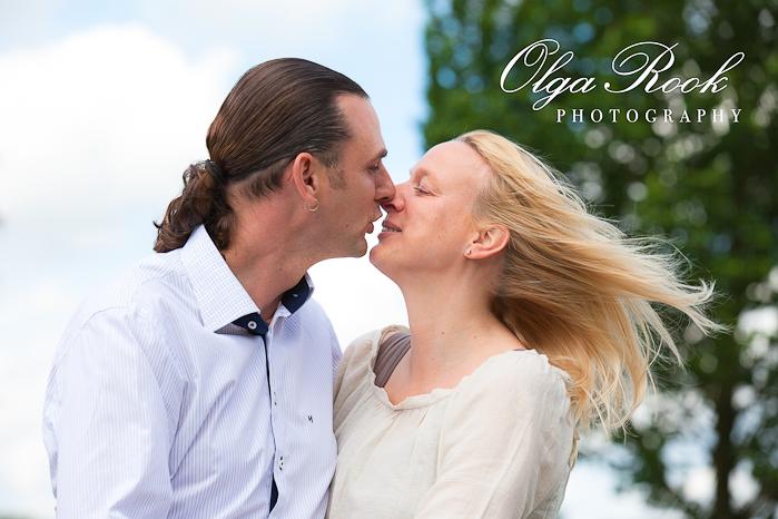 Een romantisch beeld van een mooi stel die elkaar gaat zoenen. De blonde haar van een vrouw vliegt mooi in de wind.