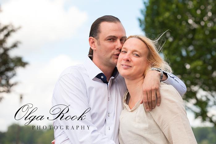 Een romantisch portret van een mooie man en vrouw op een wandeling in een park: de man heeft een zoen aan de wang van zijn vriendin.
