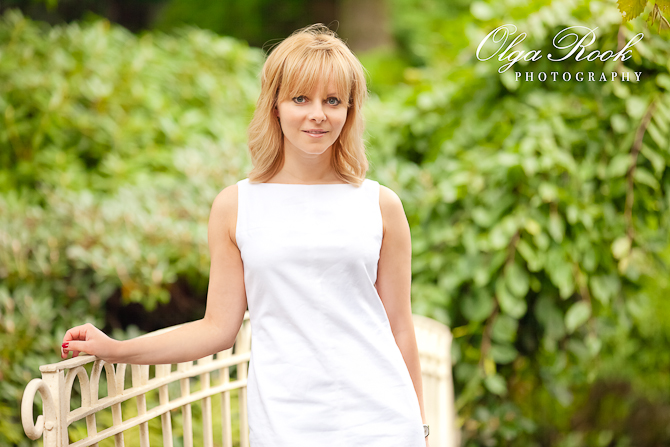 Photo of a beautiful and elegant blond woman in a park on a pretty white bridge.