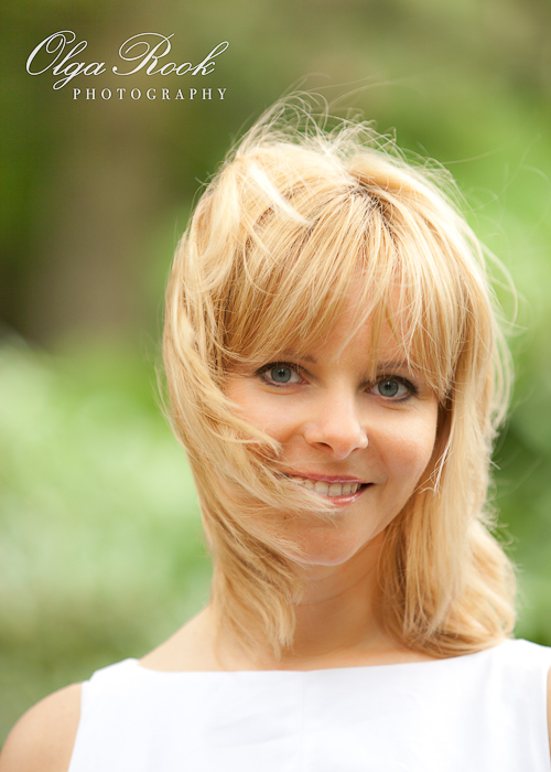 Photo of a lovely blond woman in a park, with wind in her hair and a charming smile.