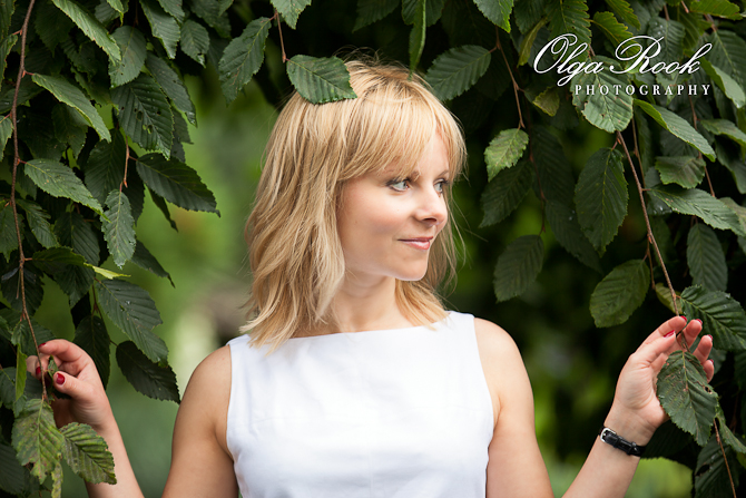 Portrait of a lovely blond lady in a park. Green branches of the trees form a kind of frame for this image.