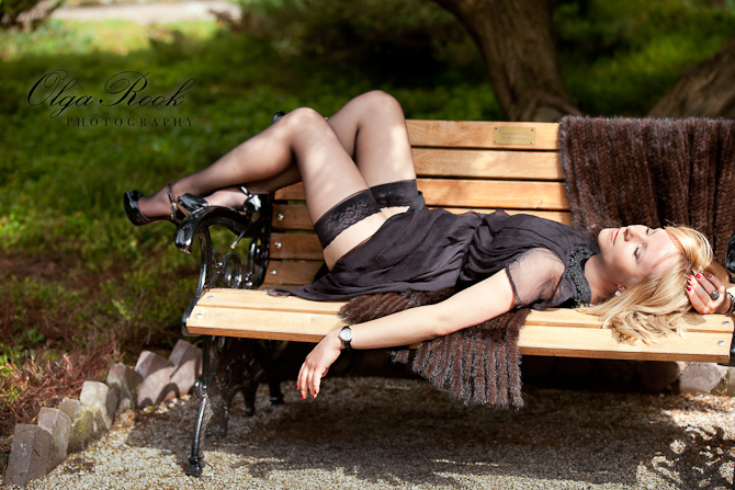 Fashion photo of an elegantly dressed young lady lying on a bench in a prak.