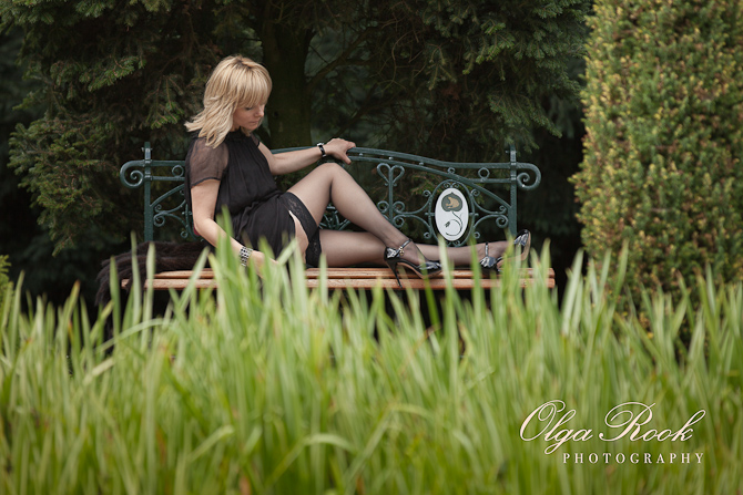 Color photograph of a blond girl on a bench in a park: photograph taken through the grass.