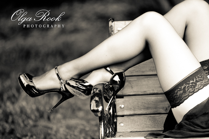 Classic black and white photo of beautiful female legs: the lady is wearing silk stockings and shoes with stilletto heels.
