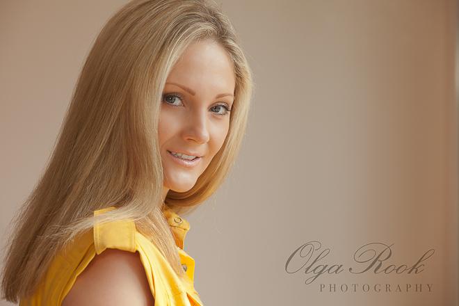 Portret van een mooie jonge vrouw met lang blond haar. Haar gele jurk heeft iets van de stijl van de jaren zeventig.