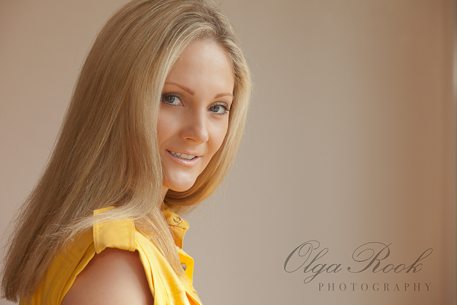 Portrait of a beautiful young lady with long blond hair. Her yellow dress evokes the style of the seventees.