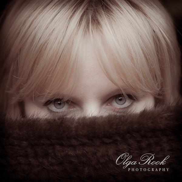 Vierkante foto met het gezicht van een mooie blonde vrouw, voor de helft verborgen achter een bontsjaal.