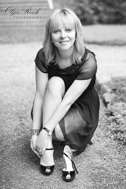 Zwartwit foto van een blonde vrouw die op een padje in een park haar schoenen wisselt: zij is bezig met schoenen met hoge hakken aantrekken en lacht naar de camera.