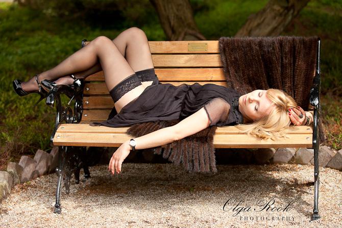 Foto van een mooie blonde vrouw die op een bankje in een park ligt. Ze draagt een fancy jurk, mooie schoenen en kousen.
