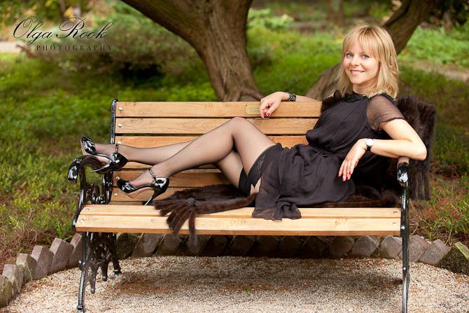 Foto van een mooie jonge vrouw op een bankje in een park: ze zit nonchalant met haar benen op het bankje en lacht.