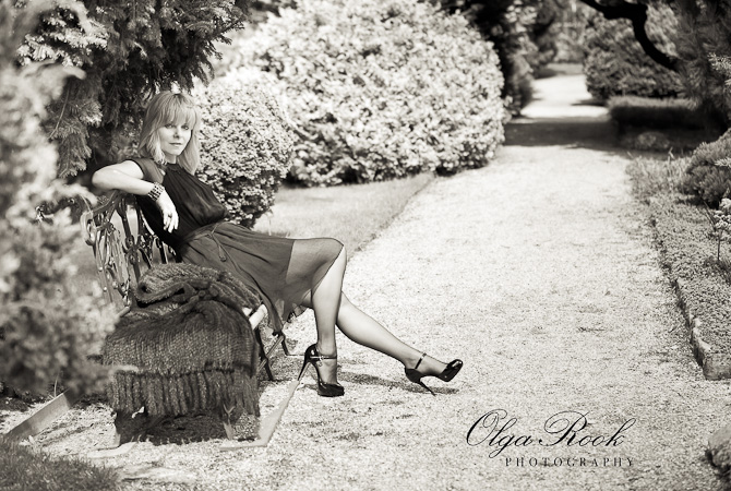 Sepia antiek ogende foto van een chique geklede jonge vrouw in een park. Ze heeft een korte jurk, hoge hakken en kijkt uitdagend.