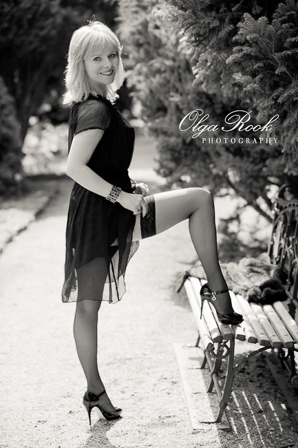 Zwartwit foto van een mooie vrouw in avondjurk in een park. Zij staat met een voet op het bankje, met zon in haar haren en lacht.