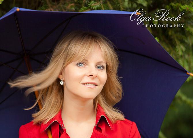 Portret van een blonde vrouw onder een paraplu.