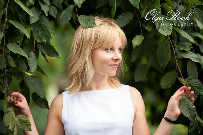 Romantische foto van een blonde vrouw die tussen de groene taken staat: ze vormen een soort kader voor de foto.