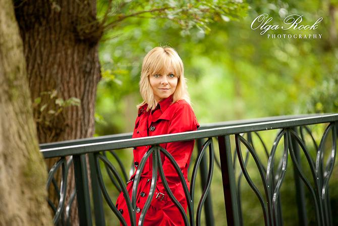 Foto van een mooie blonde vrouw in een park op een bruggetje. Zij draagt een knalrode regenjas.