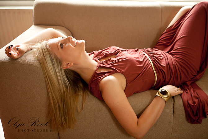 Fashion portrait of a blond model lying on a sofa, relaxed and smiling.