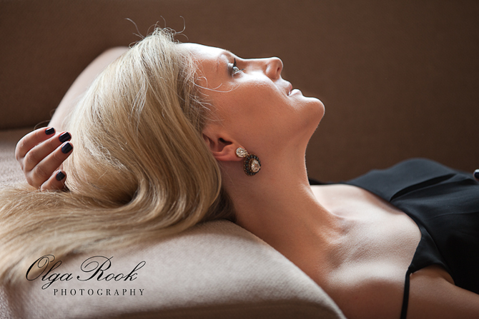 Portrait of a beautiful model en profile. A blond lady wearing classy earrings is lying on a sofa, one hand under her head.