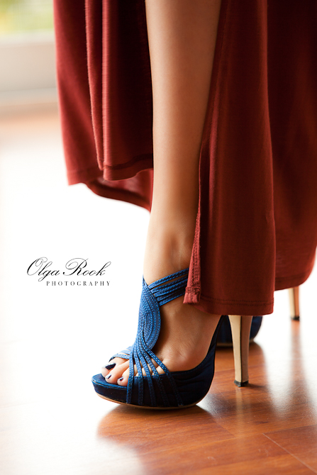 Photograph of beautiful legs of a woman, her long garment and blue shoes on stiletto heels.