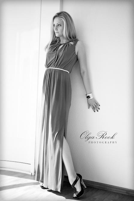 Black and white fashion portrait of a beautiful girl wearing a long dress.