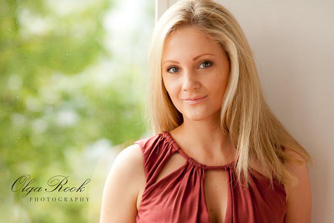 Portret van een mooie blondine voor het raam. Zachte warme licht, groene bomen achter de raam, natuurlijke en dromerige sfeer.