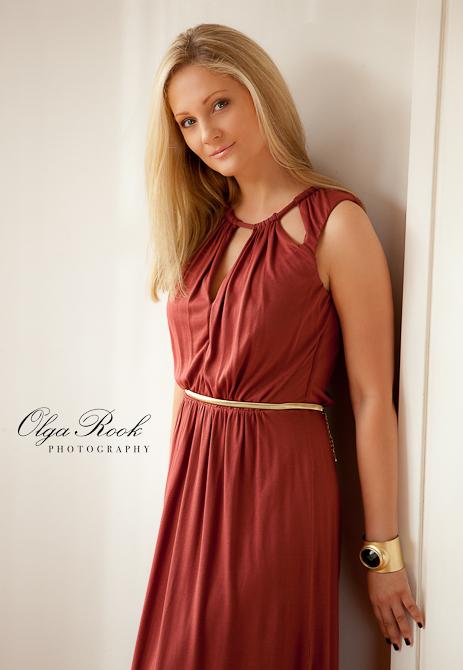Modeachtig portret van een blonde schoonheid met lange rode jurk.