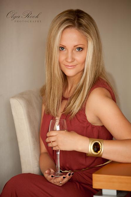 Een kleurenportret van een mooie blondine met glas wijn.