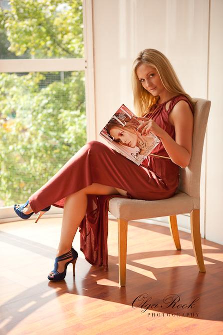 Modefotografie: portret van een mooie blonde model zittend op een stoel in een zonnige kamer. Ze draagt een lange jurk en heeft leest een modeblad.