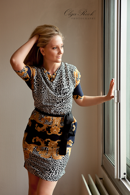 A fashion portrait of a classic beauty in front of a window, looking outside.