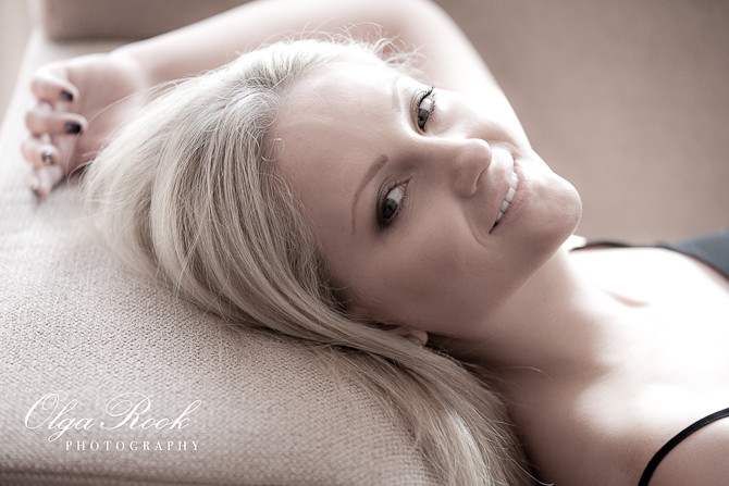 Portrait of a beautiful blond womand lying on a sofa: soft desatured colors, gentle smile, intimate atmosphere.