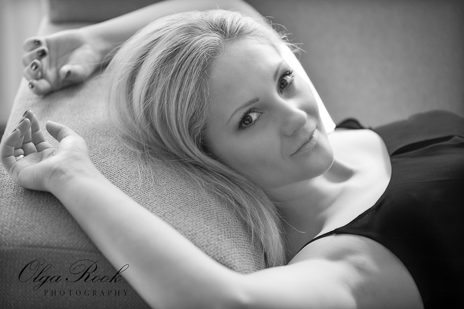 Black and white cinematic portrait of a beautiful model lying on a sofa.