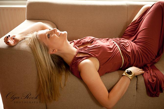 Modefotografie: foto van een blonde model liggend op een bank, lachend en dromerig.