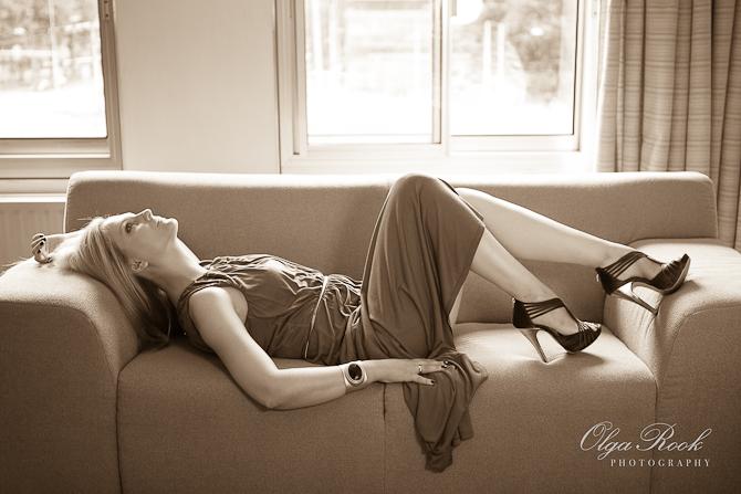 Sepia foto van een elegante blonde vrouw liggend op een bankje voor een raam. Ze draagt een lange jurk en schoenen op hoge hakken.