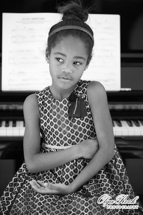 Classic black and white portrait of a little black girl sitting at a piano, pensive.