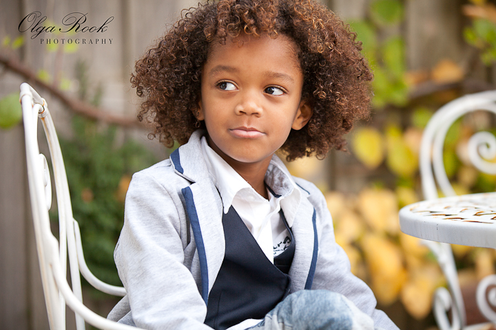 Portrait of a little curly boy. He is elegantly dressed and is sitting in the autumn garden. Romantic atmosphere, soft warm colors.