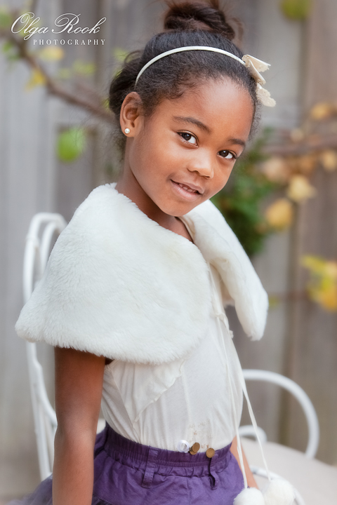 Color portrait of a small black girl standing in an autumn garden. She is wearing fancy yet elegant clothes, looks serene and dreamy.