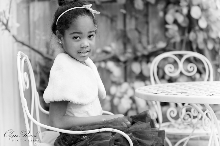 Classic black and white photo depicting a little black girl in an autumn garden. She is wearing elegant and chique clothes and is sitting on a chair at a garden table. The image is nostalgic, dreamy and romantic.