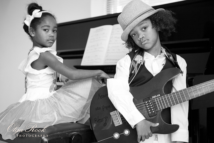 Classic black and white photo portrait of a little boy with a guitar and a little girl behind a piano. The children have chique and fancy clothes.