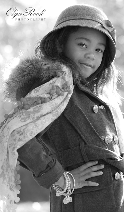 Black and white fashion photograph of a little girl wearing a hat and elegant winter clothes.